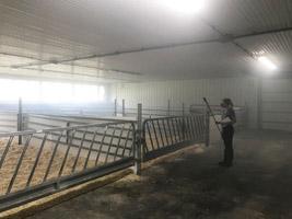 Researcher fogging barn, mist in air